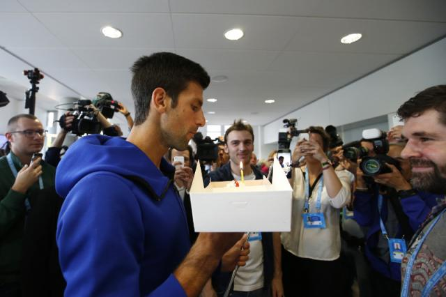 Djokovic, who turned 29, blows a candle on a birthday cake at the Roland Garros stadium on May 22 (Tanjug/AP)