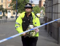 A police officer carries a floral tribute close to the Manchester Arena (Tanjug/AP)