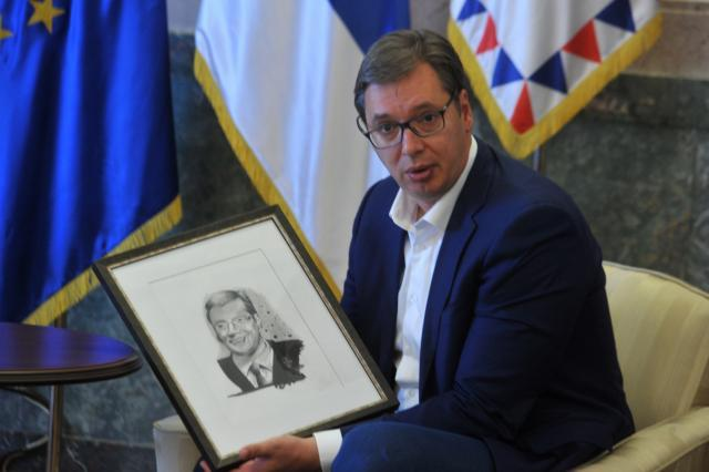 Vucic is seen with his portrait drawn by Farhad Nuri (Tanjug)