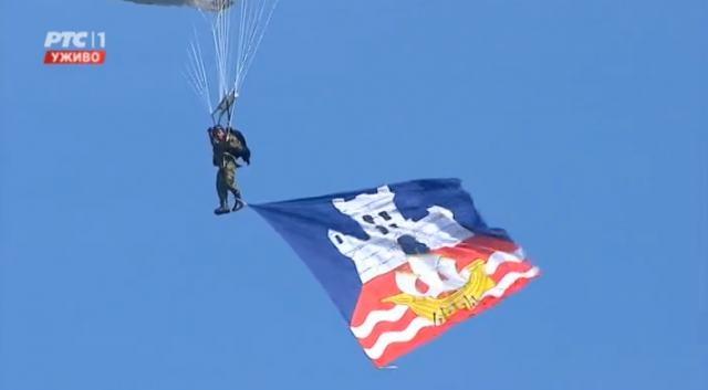 A paratrooper carries the flag of the City of Belgrade (Screen capture)