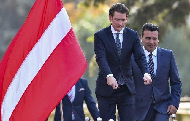 Kurz (left) is seen next to the flag of Latvia (EPA-EFE)