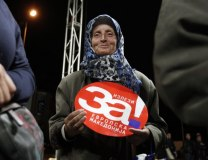 A woman holds a sign reading, 'Come out for European Macedonia& (Tanjug/AP)