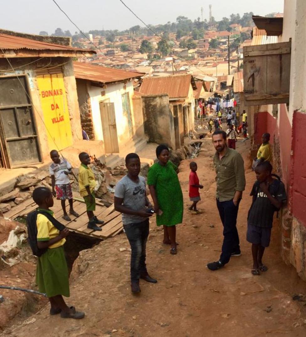 Danijel, Prudens i Džejmi sa decom u siromašnom kraju Kampale gde Prudens radi kao medicinska sestra/BBC
